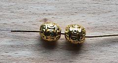 Metalen ovalen kraal 7x6mm goudkleurig, bewerkt. Per 2 stuks.
