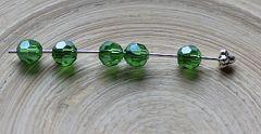 Zakje facetgeslepen glaskraal rond transparant groen met parel luster, 6mm.