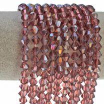Glaskraal facetgeslepen bicone roze-amethist 6mm. AB coating. Zakje van 30 stuks.